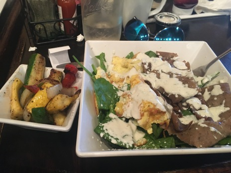 Breakfast gyro at Glory Bound served on a bed of spinach with a side of veggies.